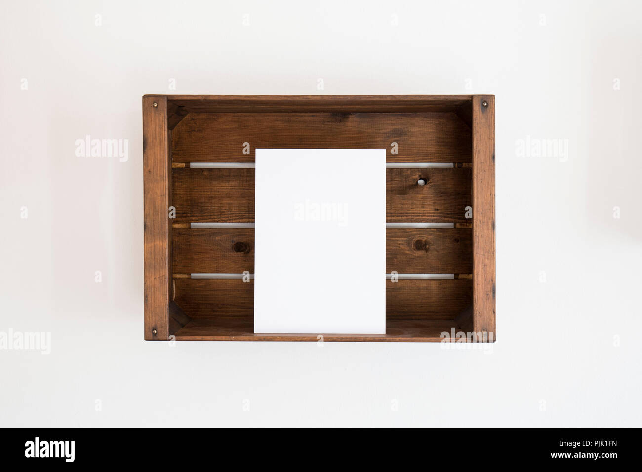 A wooden box with a white sheet of paper edgewise Stock Photo