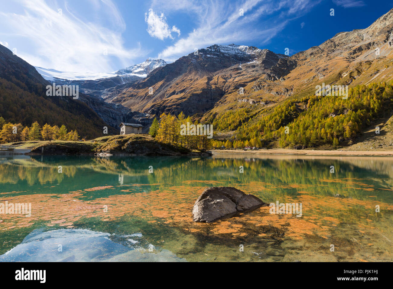 The afternoon sun bathes the area around the reservoir Lago Palü on the Alp Grüm near Poschiavo in an autumnal light, canton Grisons, Switzerland, - Stock Image