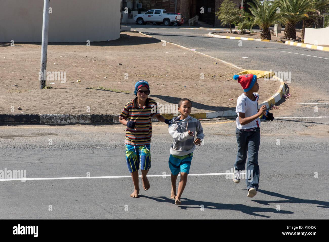Children running crossing a street in Keetmanshoop, Namibia. Street scene in Keetmanshoop, Namibia - Stock Image