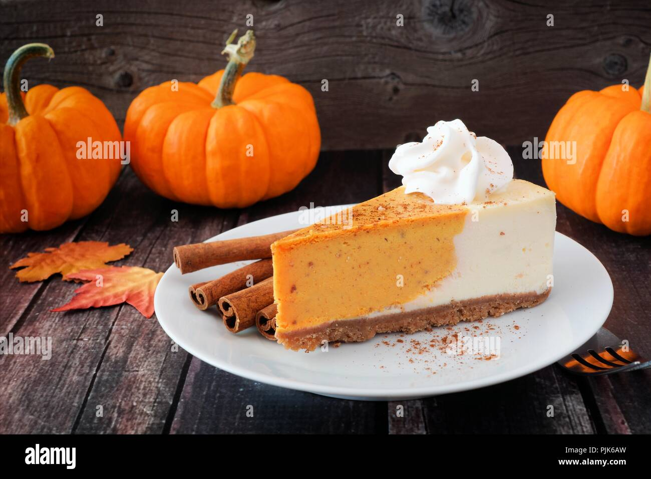 Slice of pumpkin cheesecake with whipped cream on a dark rustic wood background - Stock Image