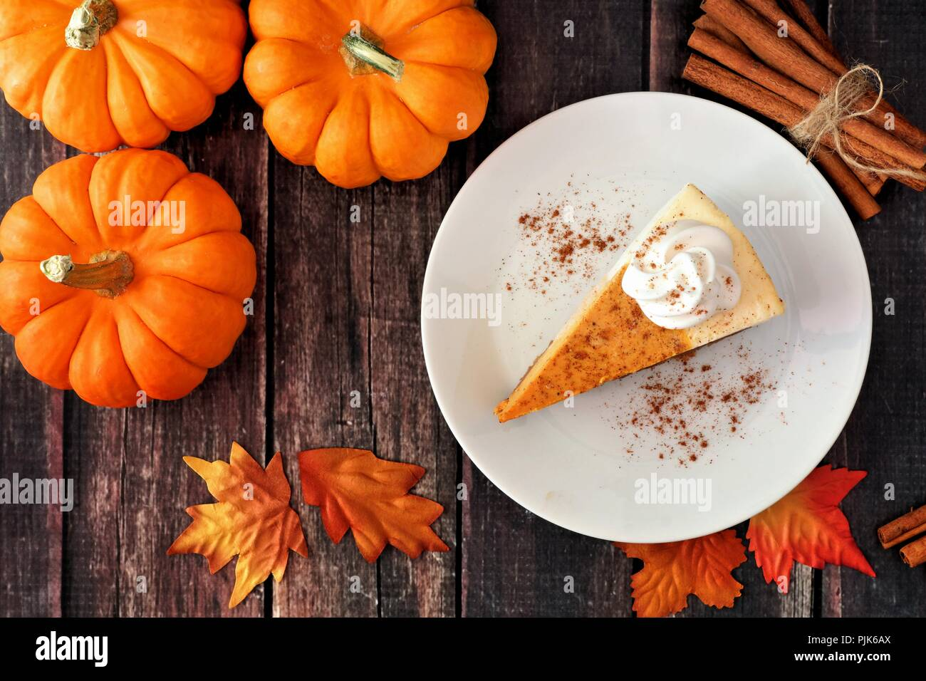 Slice of pumpkin cheesecake with whipped cream, top view on a rustic wooden background - Stock Image