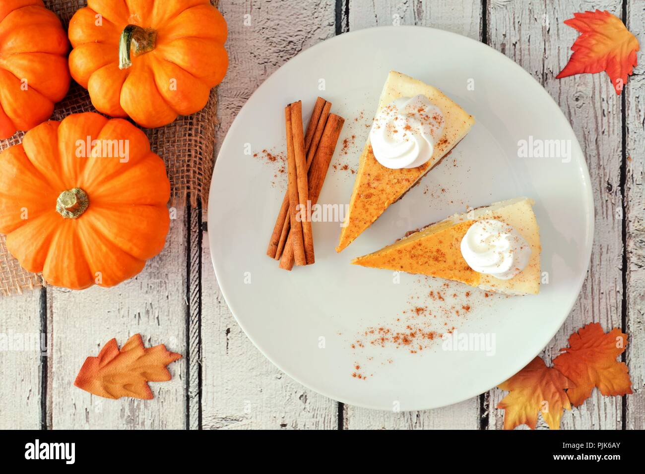 Plate with two slices of pumpkin cheesecake with whipped cream, overhead view on a white wood background - Stock Image