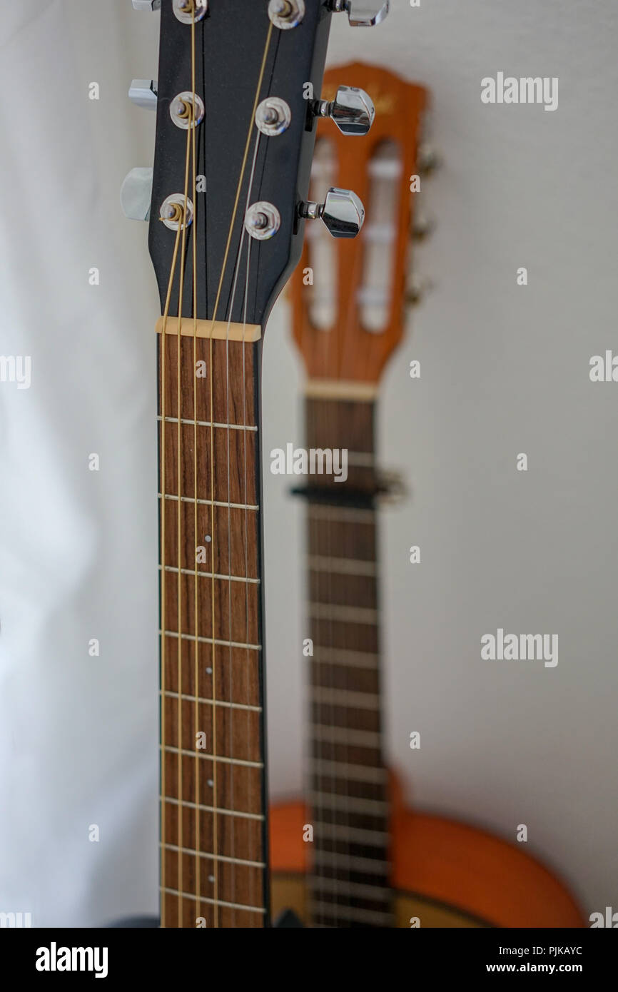 two guitras standing in front of a white wall with capo - Stock Image