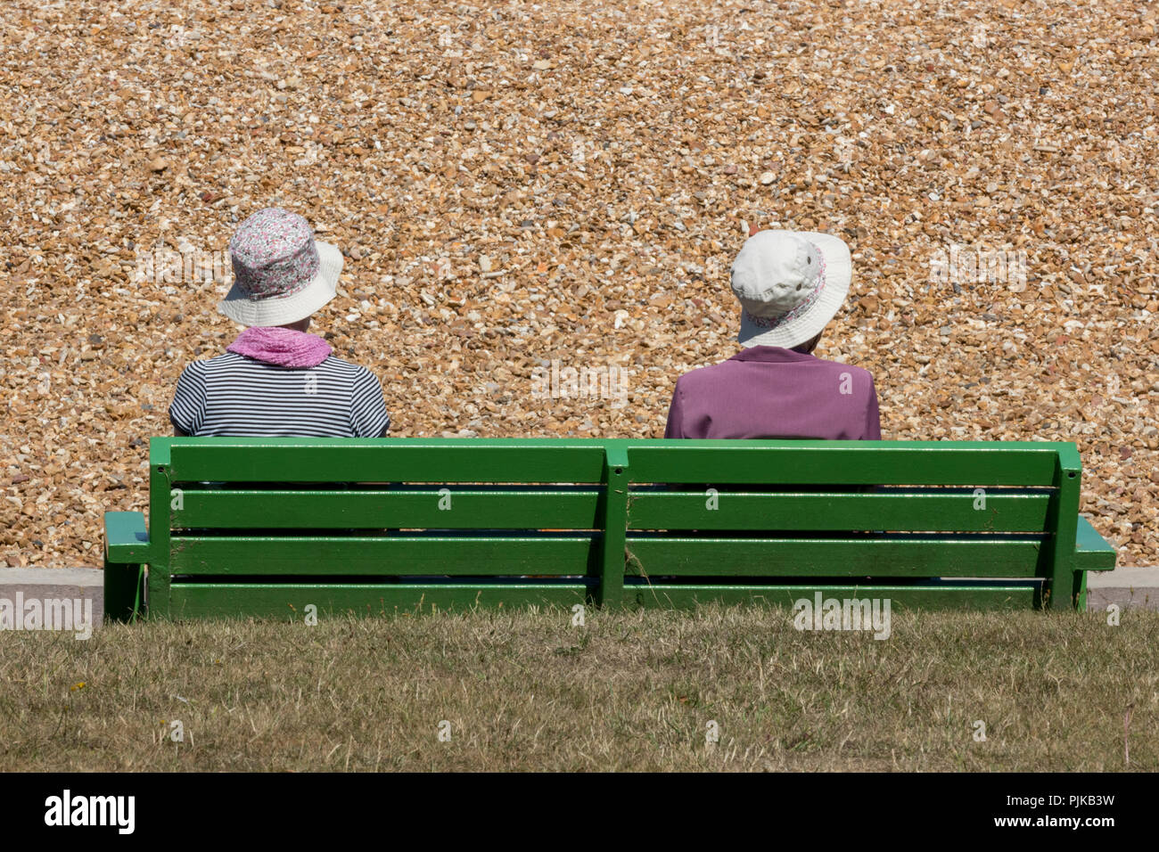 two elderly people or a retired couple sitting on a green painted park bench at the seaside in cowes on the isle of wight. retired couple at coast. - Stock Image