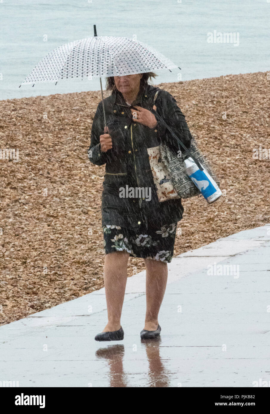 older or middle aged woman walking along a seaside pathway in the rain with an umbrella to protect against the wet weather and downpour. - Stock Image