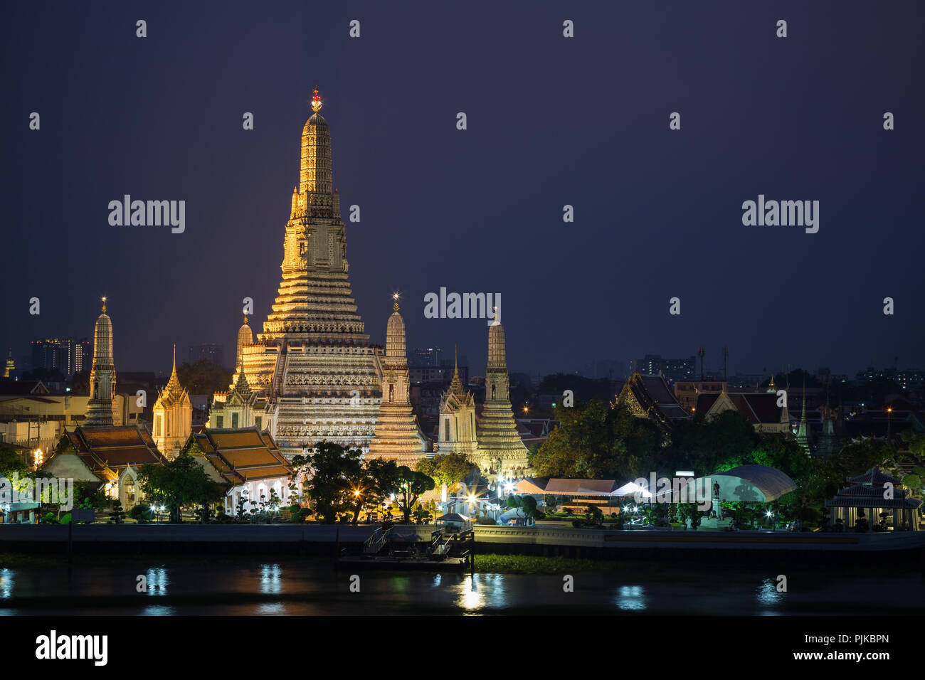 Beautiful view of lit Wat Arun temple next to Chao Phraya River in Bangkok, Thailand, in the evening. - Stock Image