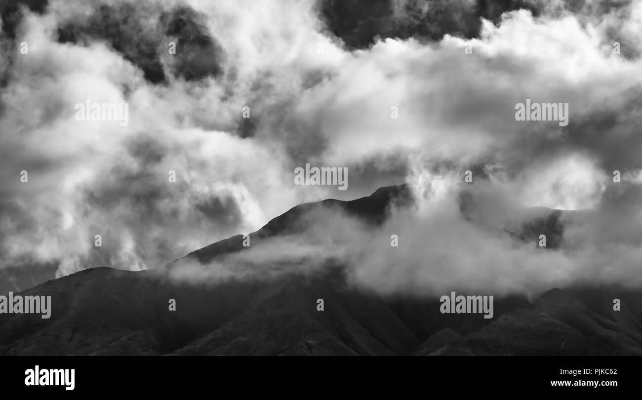 Black and White Mountain Ridge with Clouds Above and Below - Stock Image