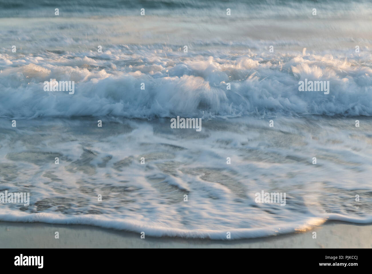 Evening sunlight lighting up waves rolling in on the beach at Trearddur Bay, Anglesea, North Wales - Stock Image