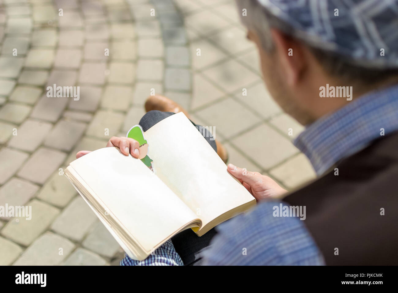 back over his shoulder to see what the man in the hat sitting legs crossed and reading a book. - Stock Image
