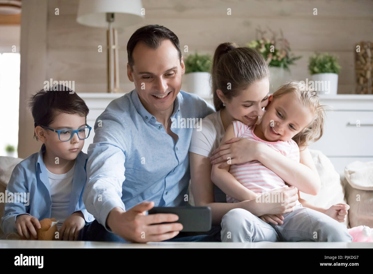 Smiling father making selfie of happy family of four - Stock Image