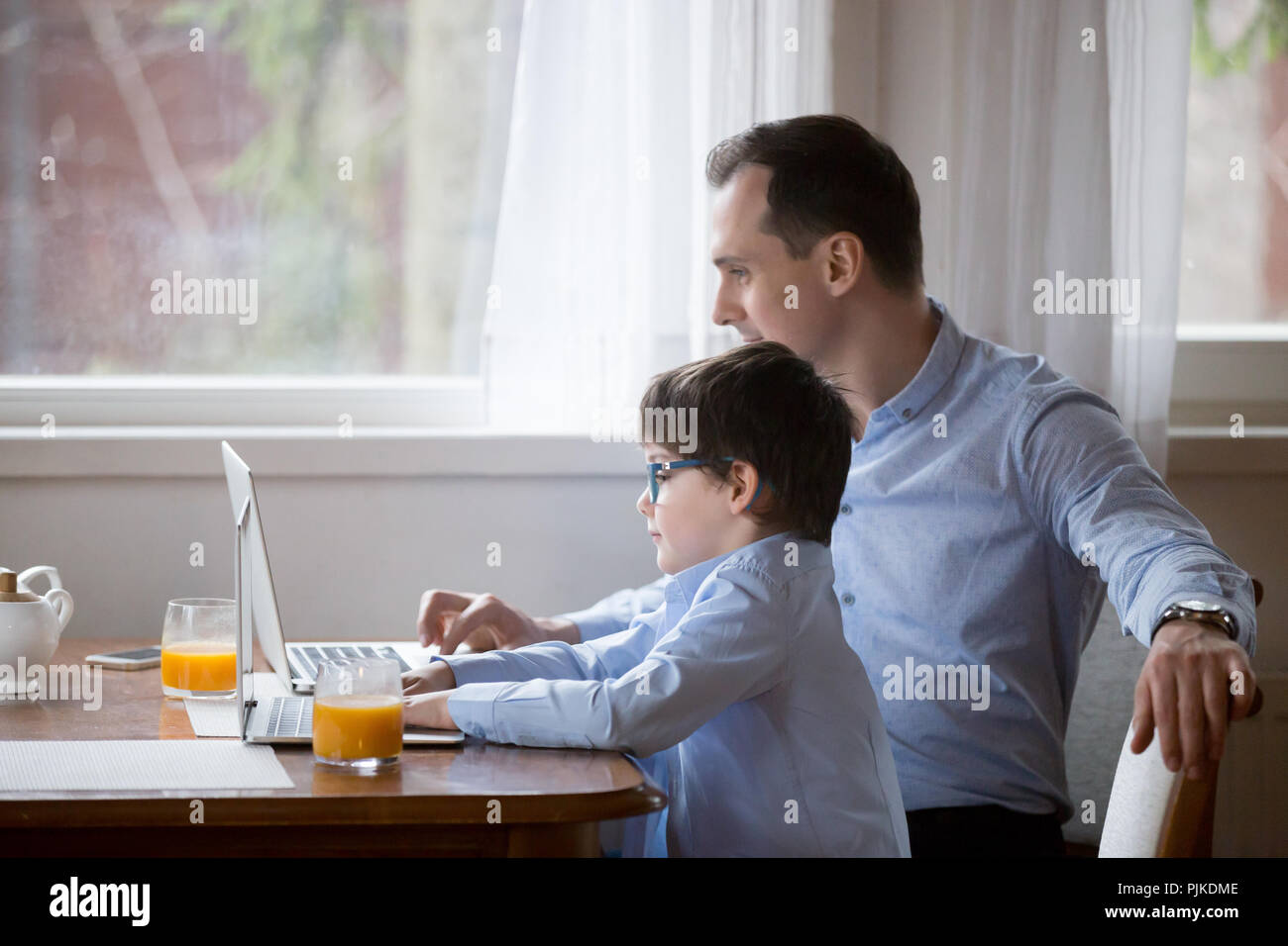 Cute boy and dad working at laptops in kitchen together - Stock Image