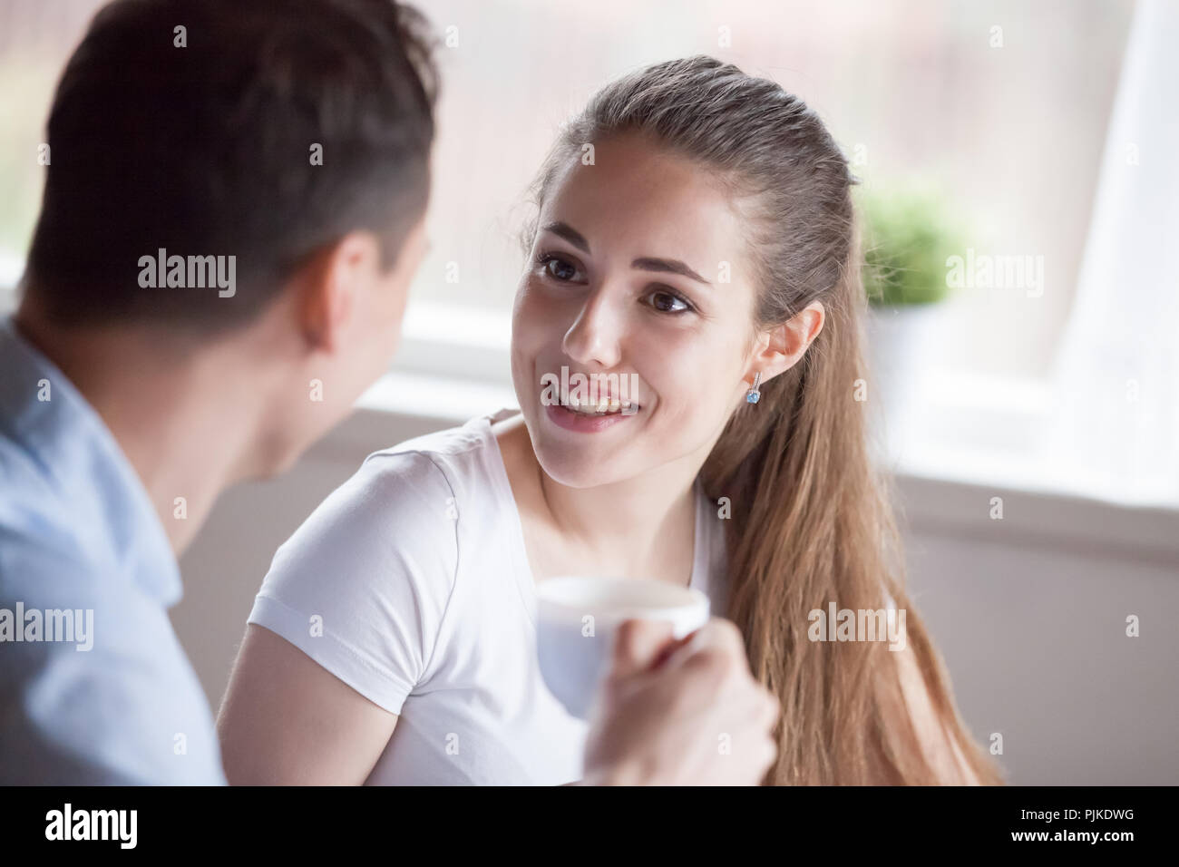 Close up of curious happy woman listening to man talking - Stock Image