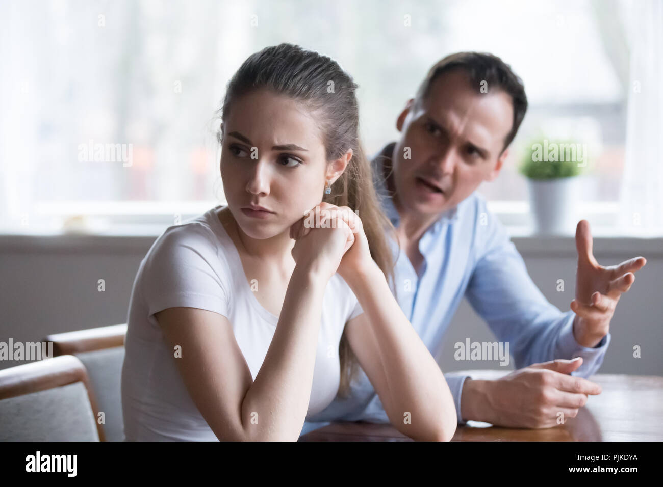 Mad man screaming or lecturing offended young lover - Stock Image