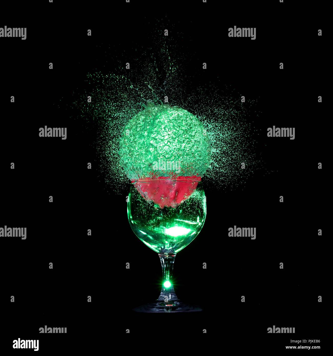 bursting water-filled balloon with wine glass, studio shot - Stock Image