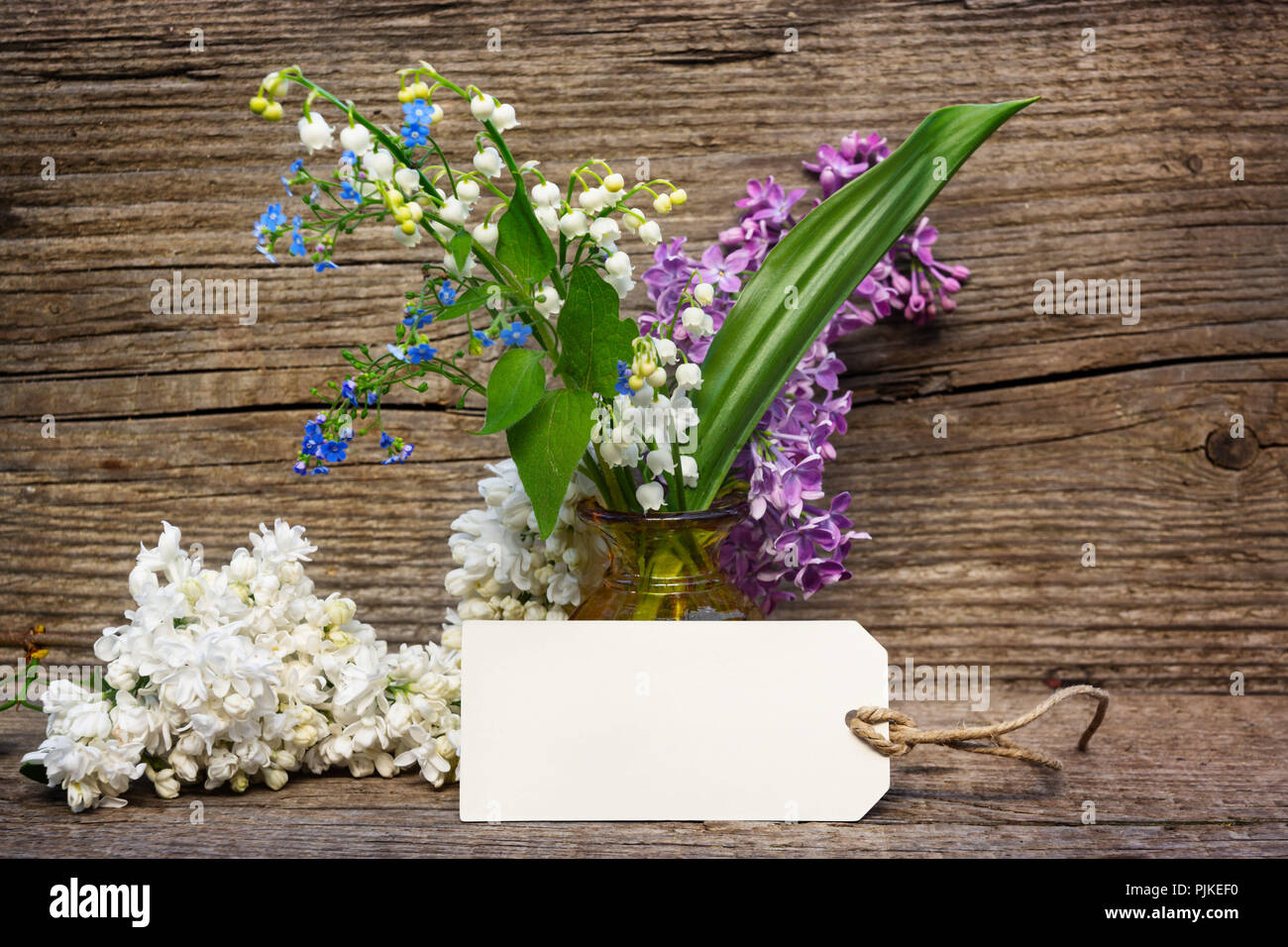 Greeting card with lilac, lily of the valley and forget-me-not on wood - Stock Image