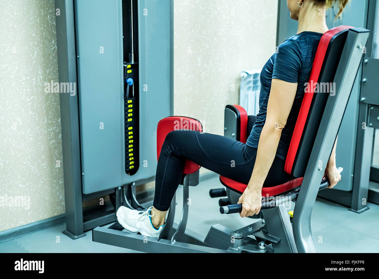 Side view young woman does leg exercises in gym - Stock Image