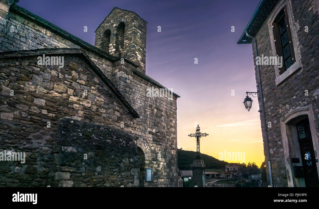 The Romanesque church of Saint-Étienne in Minerve, consecrated in 453, crucifix, evening mood - Stock Image