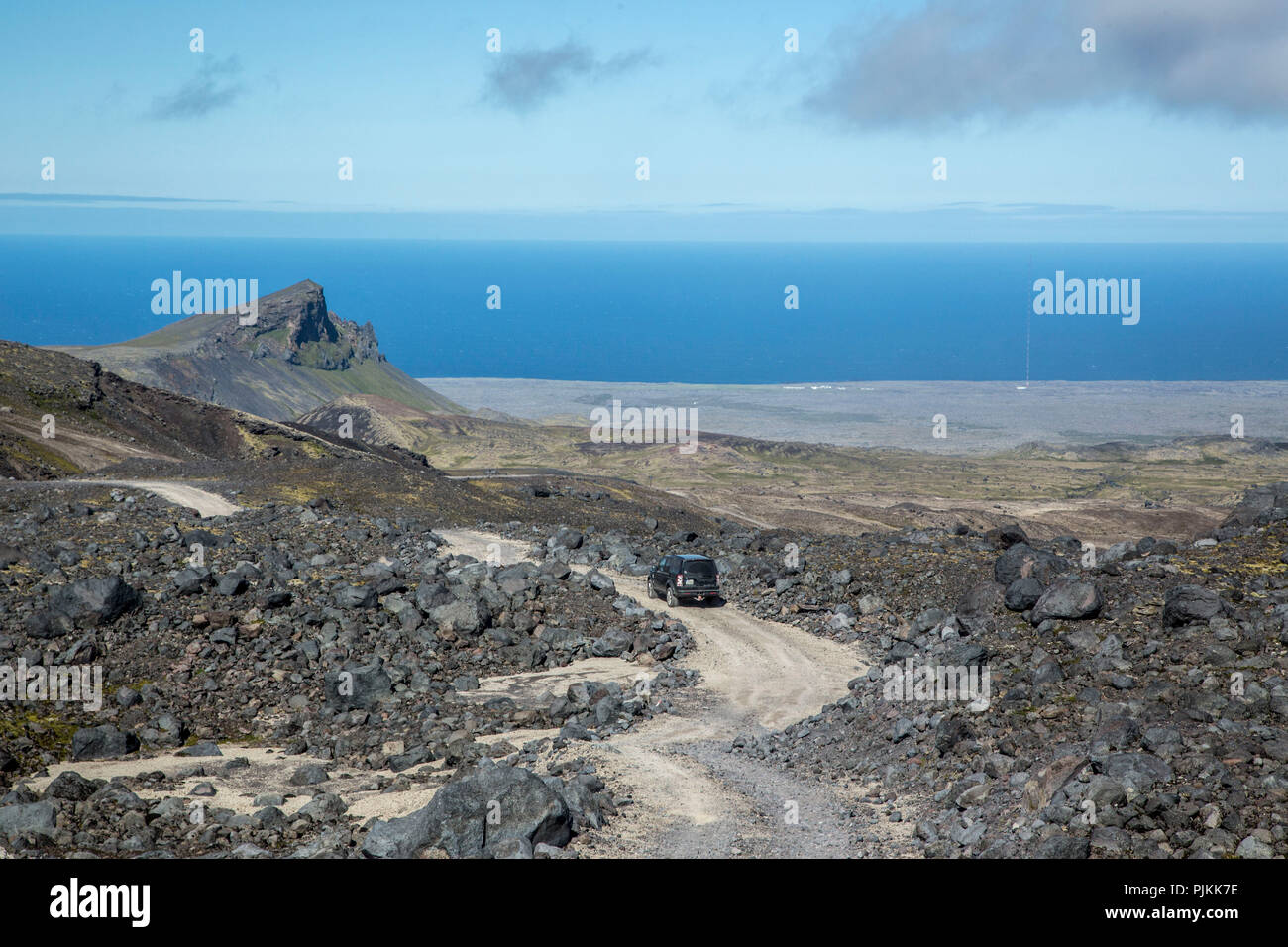 Piste to Snaefellsjökull, all terrain vehicle in the lava field, Breidafjord in the background, blue sky over blue sea - Stock Image