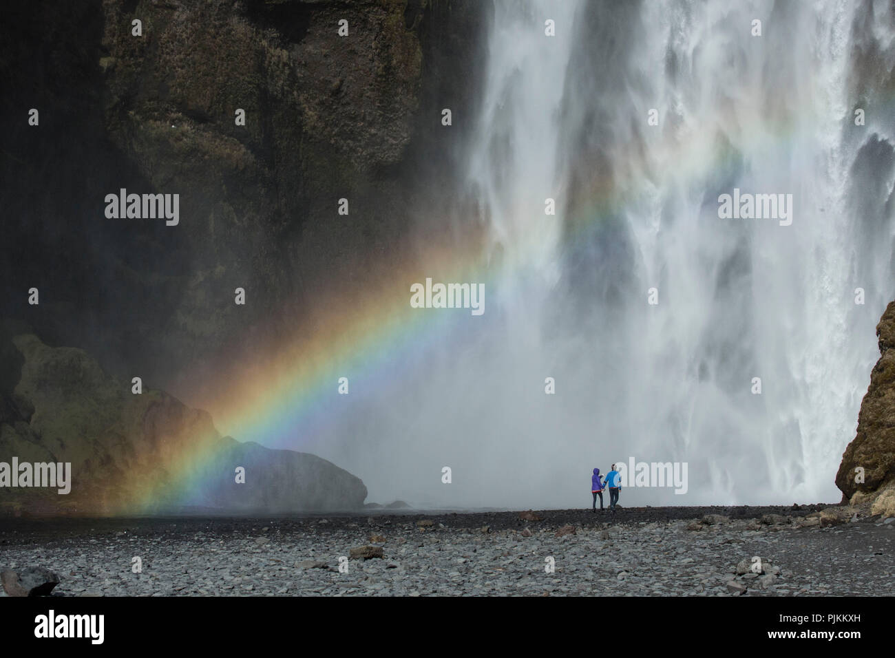 Europe, Northern Europe, Iceland, Skógar, couple standing in front of the mighty Skógafoss in southern Iceland, rainbow - Stock Image