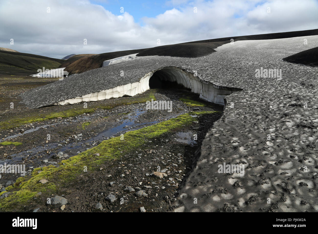 Iceland, Fjallabak, snowfield, old snow covered with volcanic ash in summer, meltwater - Stock Image