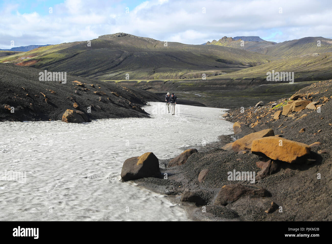 Iceland, two hikers on a snow field in the lava desert, mountains in the background, black sand and orange stones - Stock Image