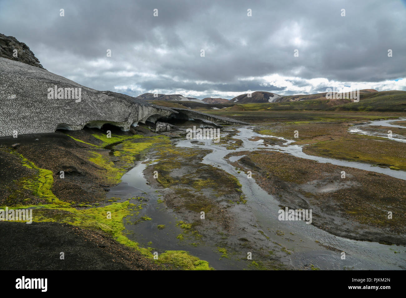 Iceland, Fjallabak, snow field, old snow, covered with volcanic ash, green moss, in summer, melt water, dark clouds - Stock Image