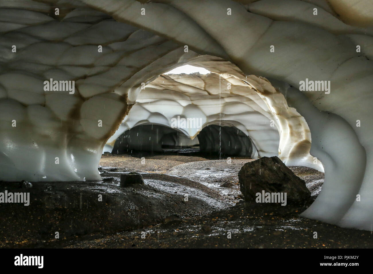 Iceland, snow cave washed by the stream, water flowing from the ceiling - Stock Image