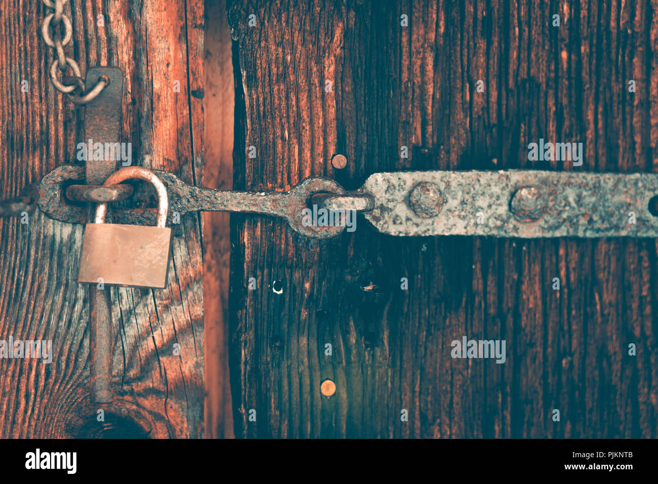 A wooden door is secured with a latch and a padlock, - Stock Image