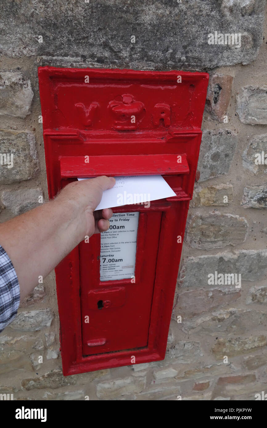 Mans hand posting letter into an English village post box that is built into large stone wall - Stock Image