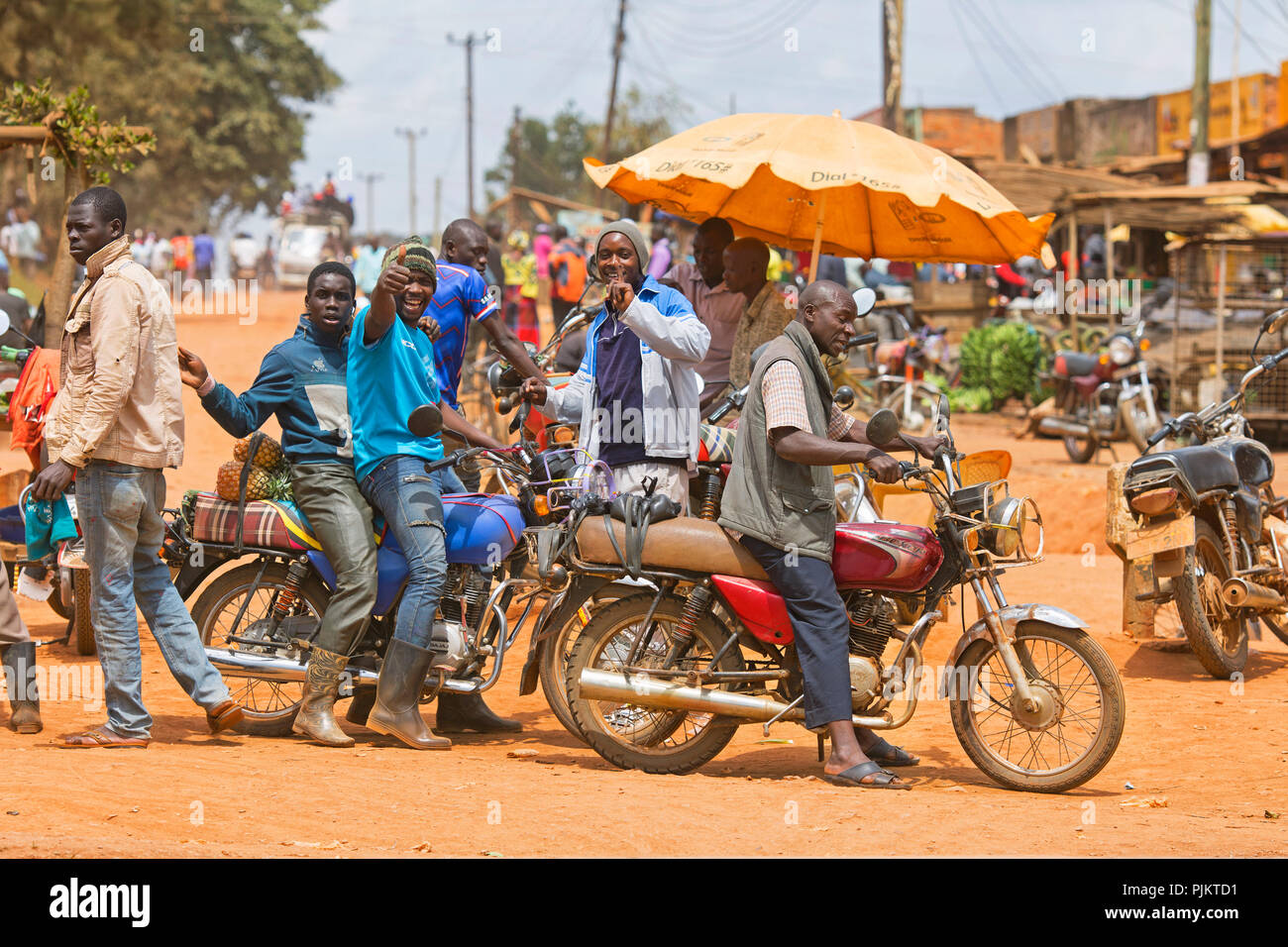 Small Town, Street Scene, Men with Motorcycles Local Transport, Motorbike Taxis, Uganda, East Africa - Stock Image