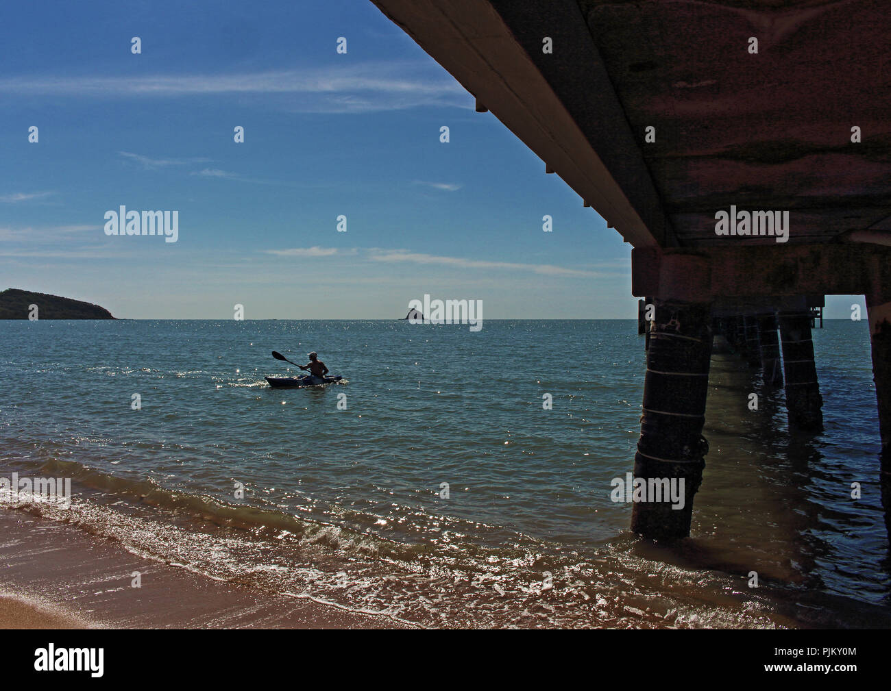 View from under the famous jetty of a kayak paddling into the beach at Palm Cove, a beautiful northern beach suburb just 25km out of Cairns - Stock Image