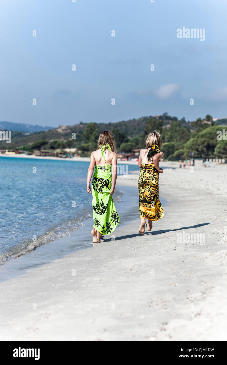 Two girls in beach dresses walking on the sandy, lonely beach of Palombaggia, Corsica - Stock Image
