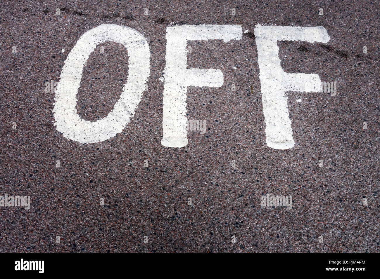 The word 'Off' written on road surface in car park - Stock Image