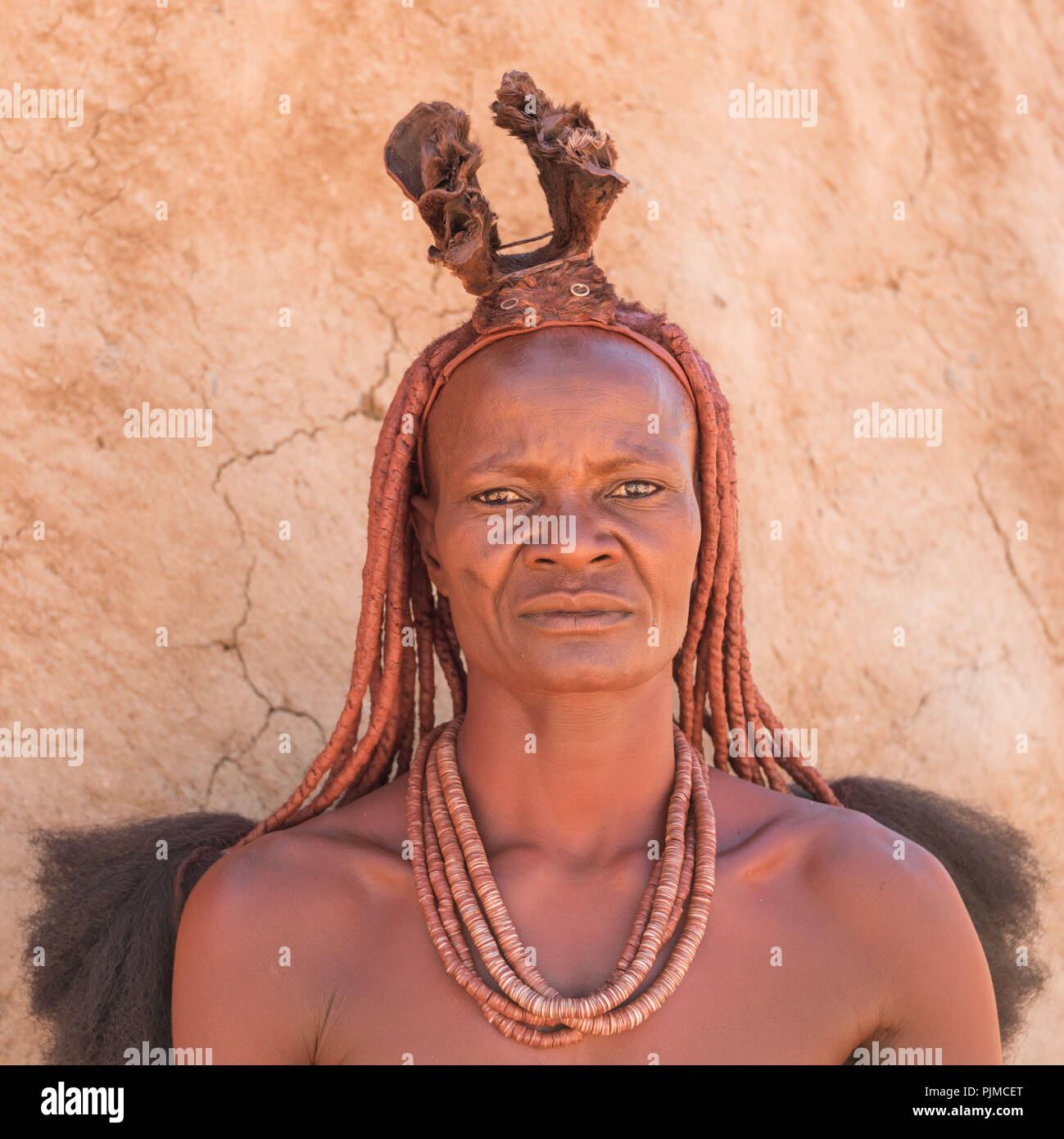 Portrait of a Himba woman with traditional headgear, looking into the camera - Stock Image