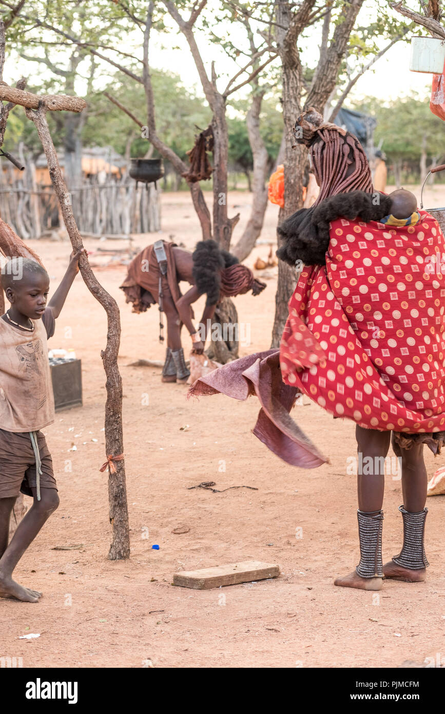 Spirit of optimism in the Himba village: Two Himba women gather their things together in the late afternoon, a Himba boy is watching - Stock Image