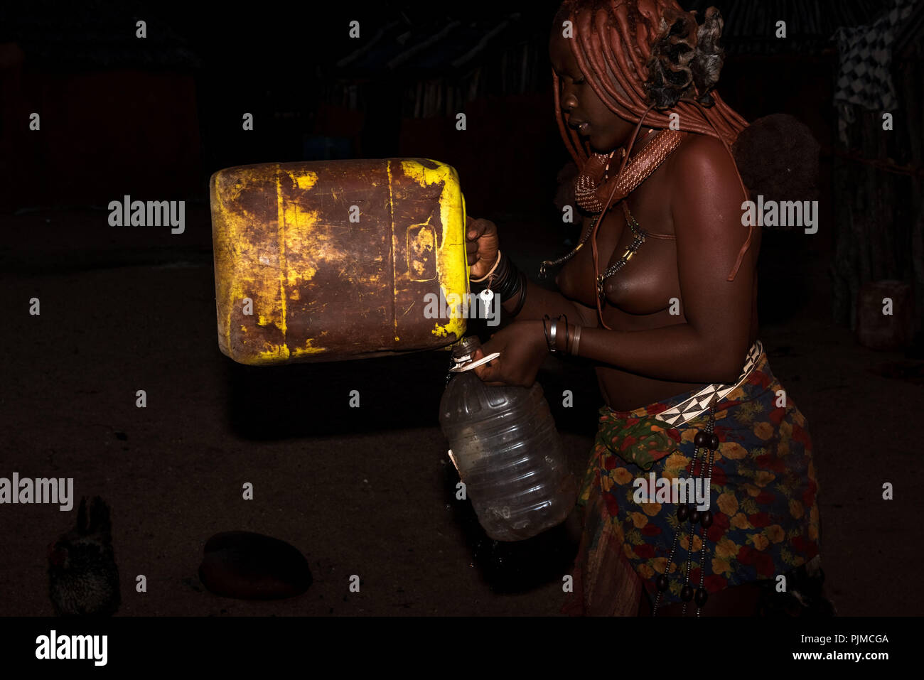 Young Himba woman pouring collected rainwater, a rarity in Namibia, from a canister into a plastic bottle - Stock Image