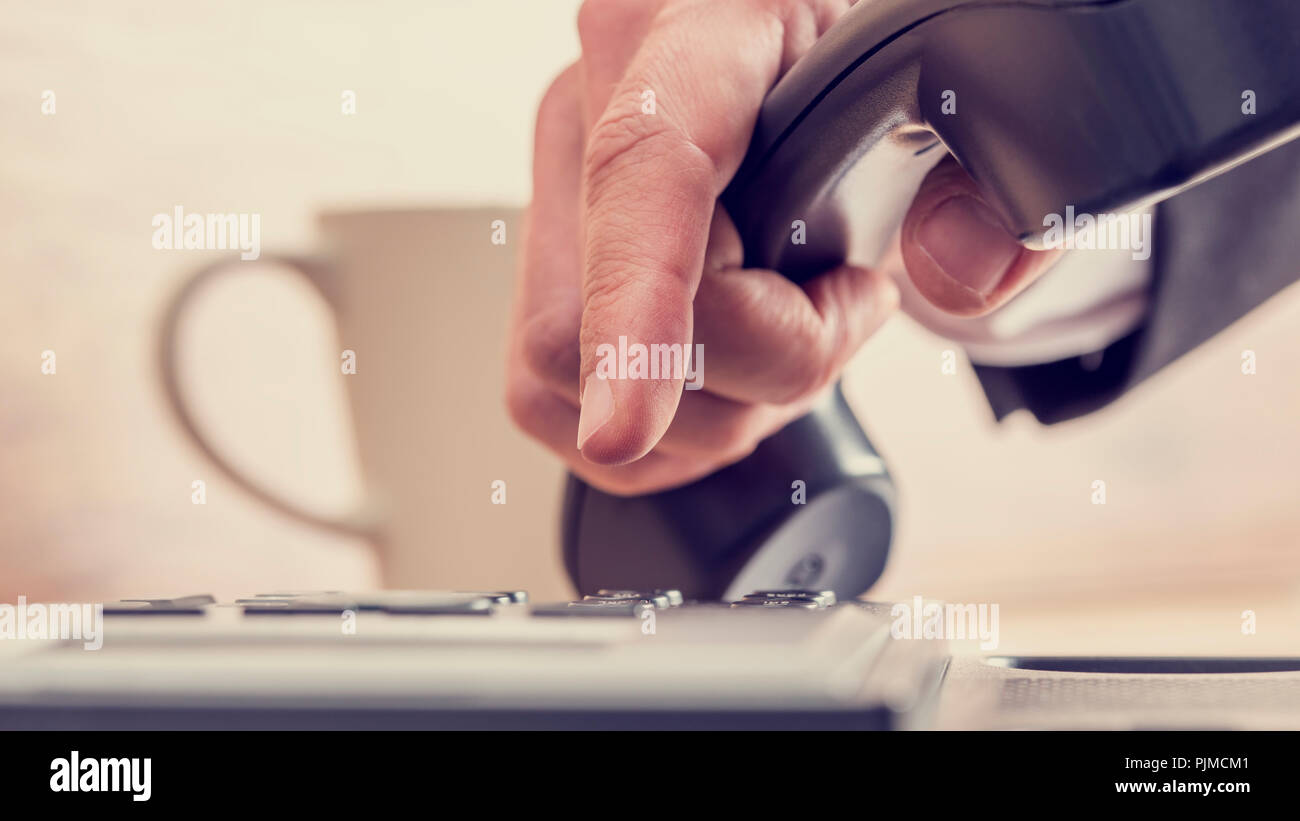 Retro image of male hand dialing a telephone number on a black phone with cup of coffee in background. - Stock Image