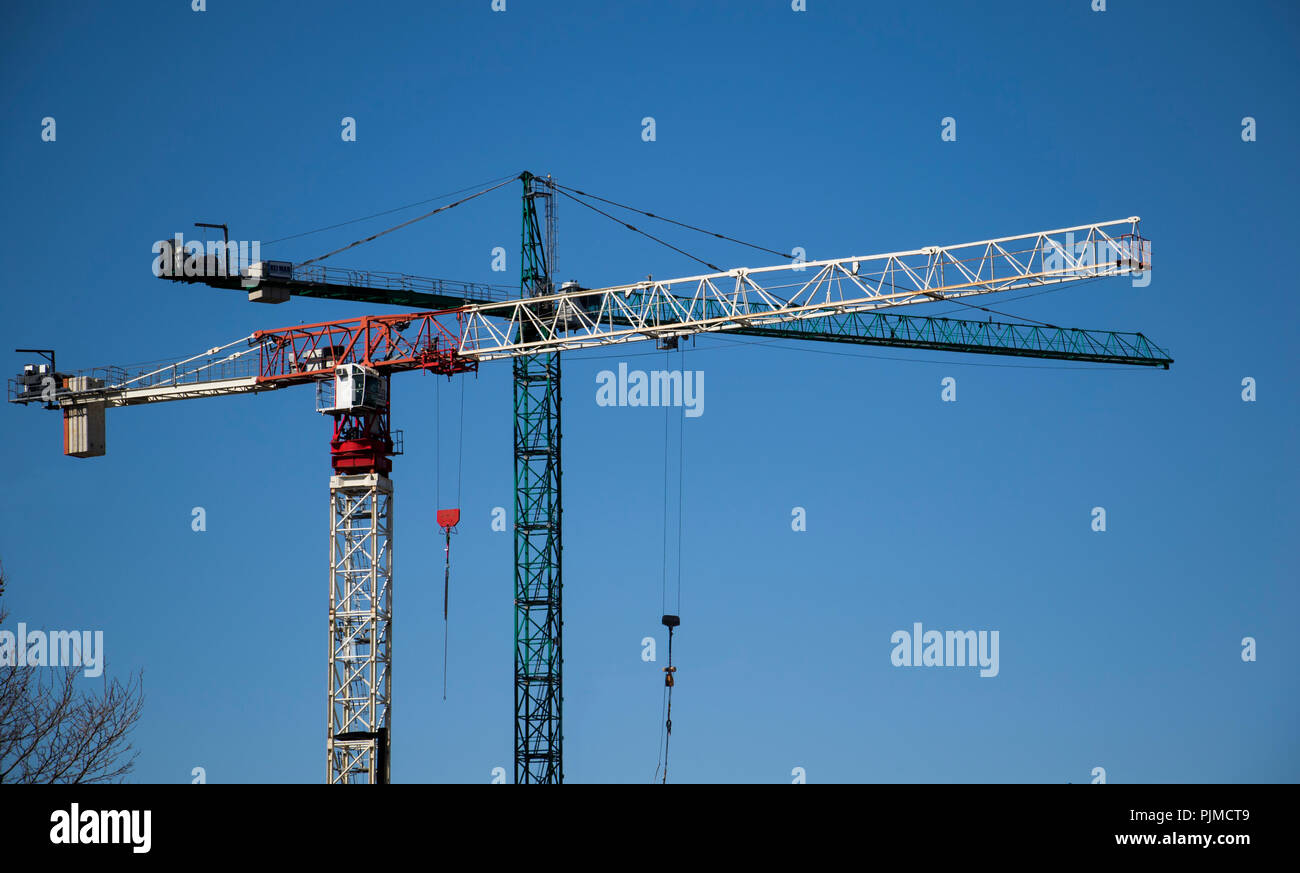 Two construction cranes moving and working during the day time. High rise building and condo architecture construction. Heavy lift machinery. - Stock Image