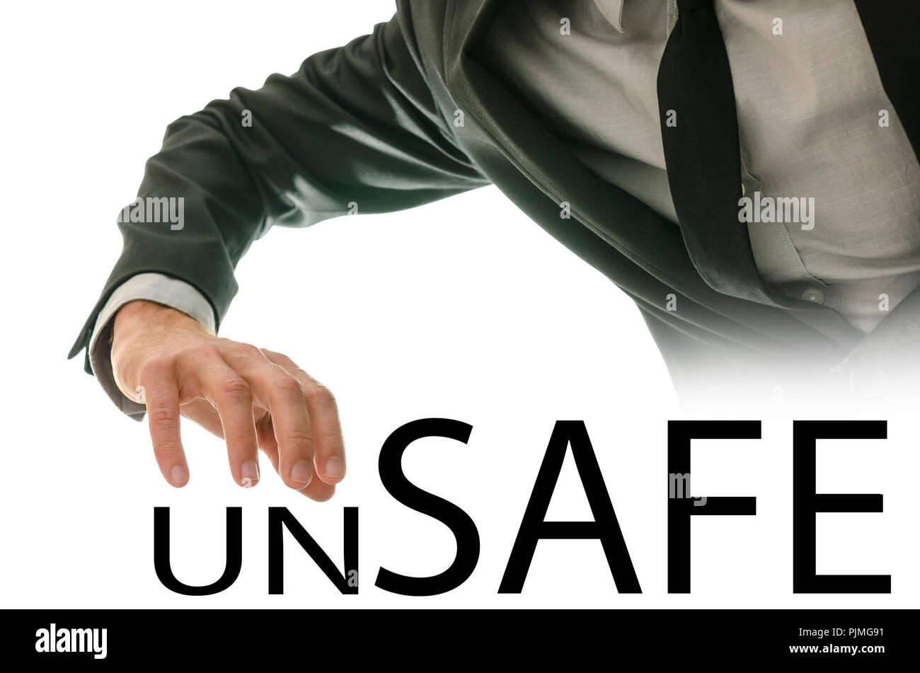 Businessman reaching his hand for the text Unsafe - Safe in a conceptual image of opposites between being secure or unsafe and open to risk. - Stock Image