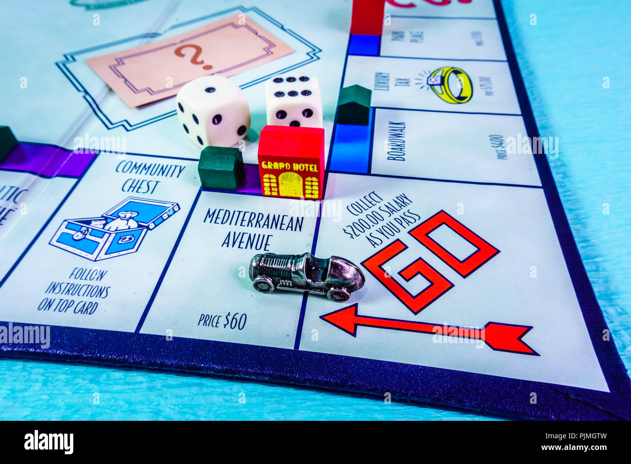 Monopoly Board Game close up with the car passing the GO. The classic real estate trading game from Parker Brothers. - Stock Image