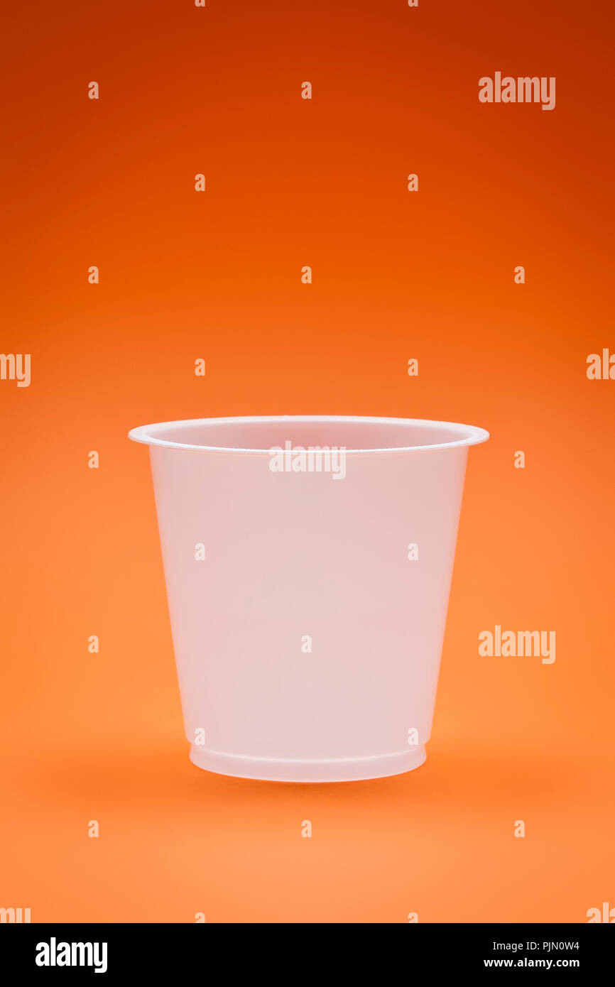 An image of a white empty plastic cup on an orange background - Stock Image