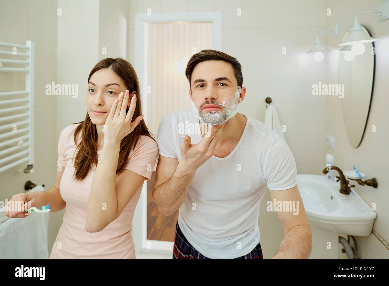 Couple in the morning personal hygiene in the bathroom - Stock Image