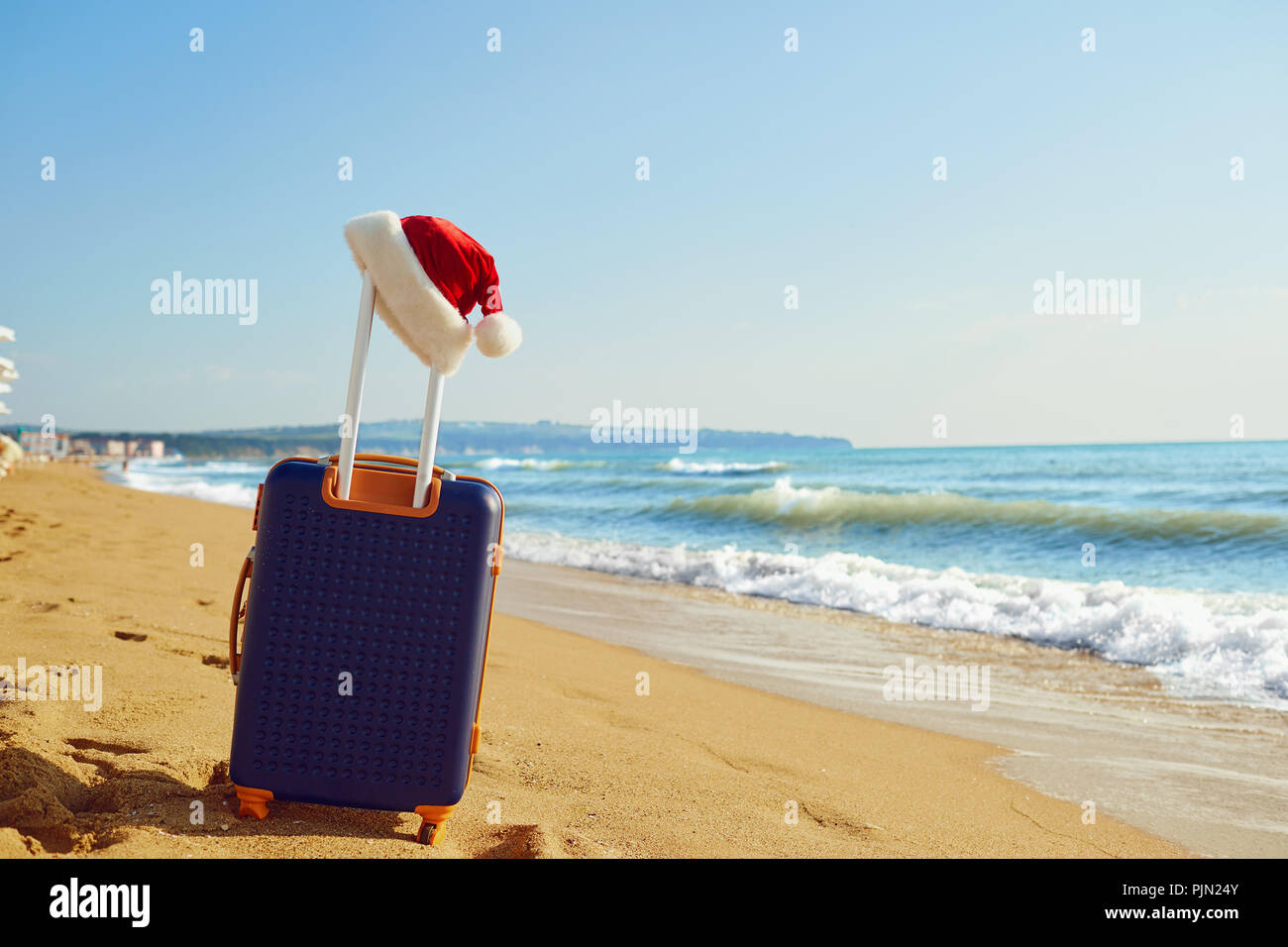 Christmas Beach.Santa Claus Hat On A Suitcase On The Beach By The Sea