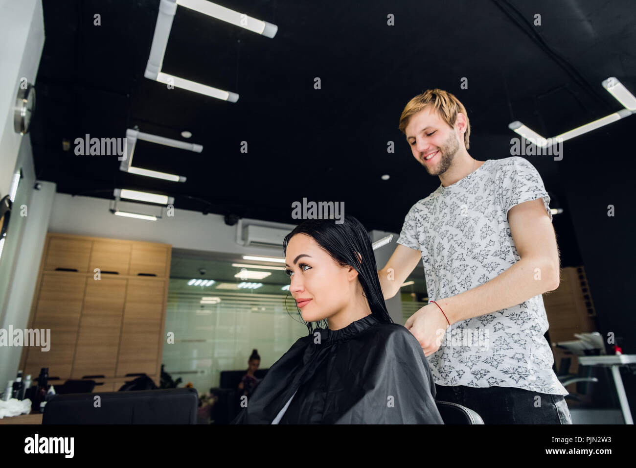 Professional hairdresser discussing female customer preferences in barbershop, choosing new hairdo - Stock Image