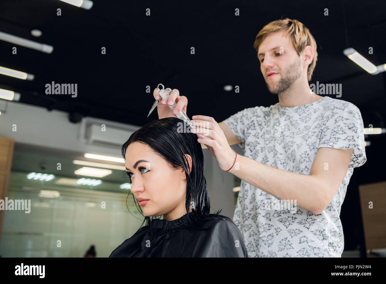Hairdresser creating a hairstyle for beautiful woman closeup - Stock Image