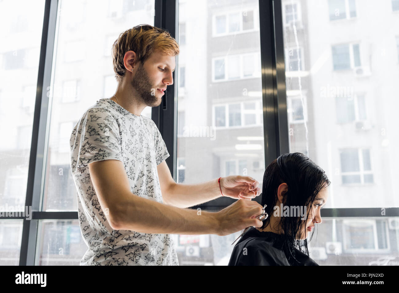 Hairdresser cutting hair of a beautiful serious brunette woman - Stock Image