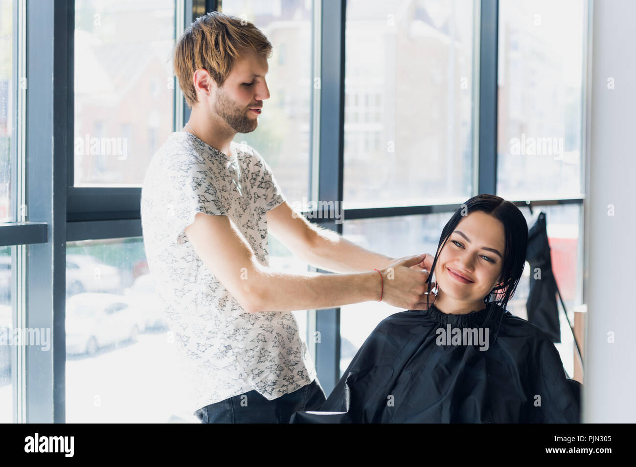 A woman in a hairdressing salon waiting to see the results looking in a mirror, smiling and talking with artist - Stock Image