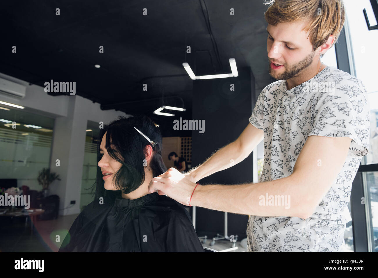 Hairstylist with comb and scissors cutting hair of female client. Woman in hairdressing beauty salon. - Stock Image