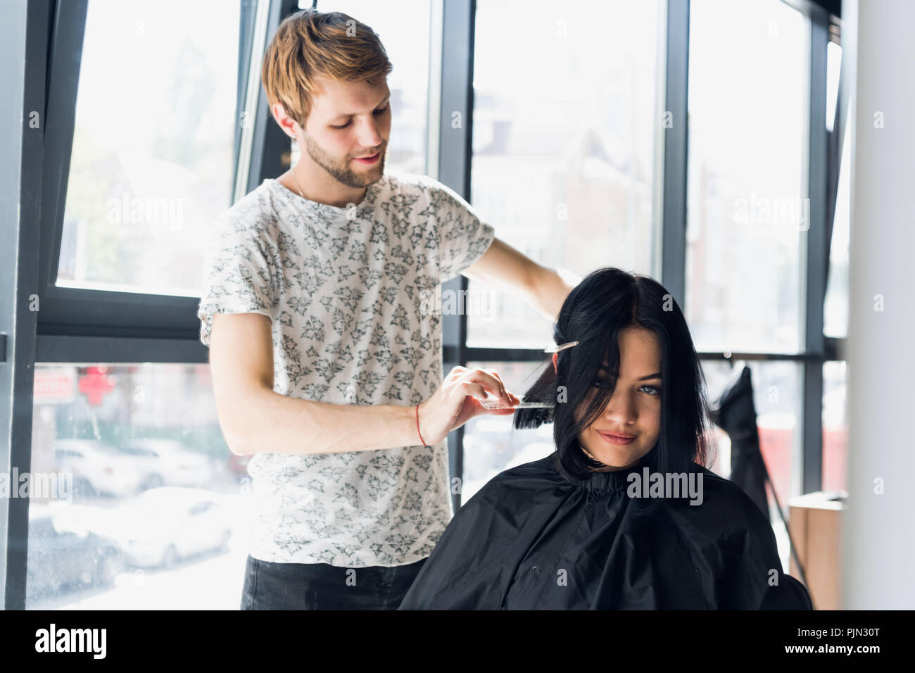 Going for a change of style. Young beautiful woman discussing hairstyling with her hairdresser while sitting in the hairdressing salon - Stock Image