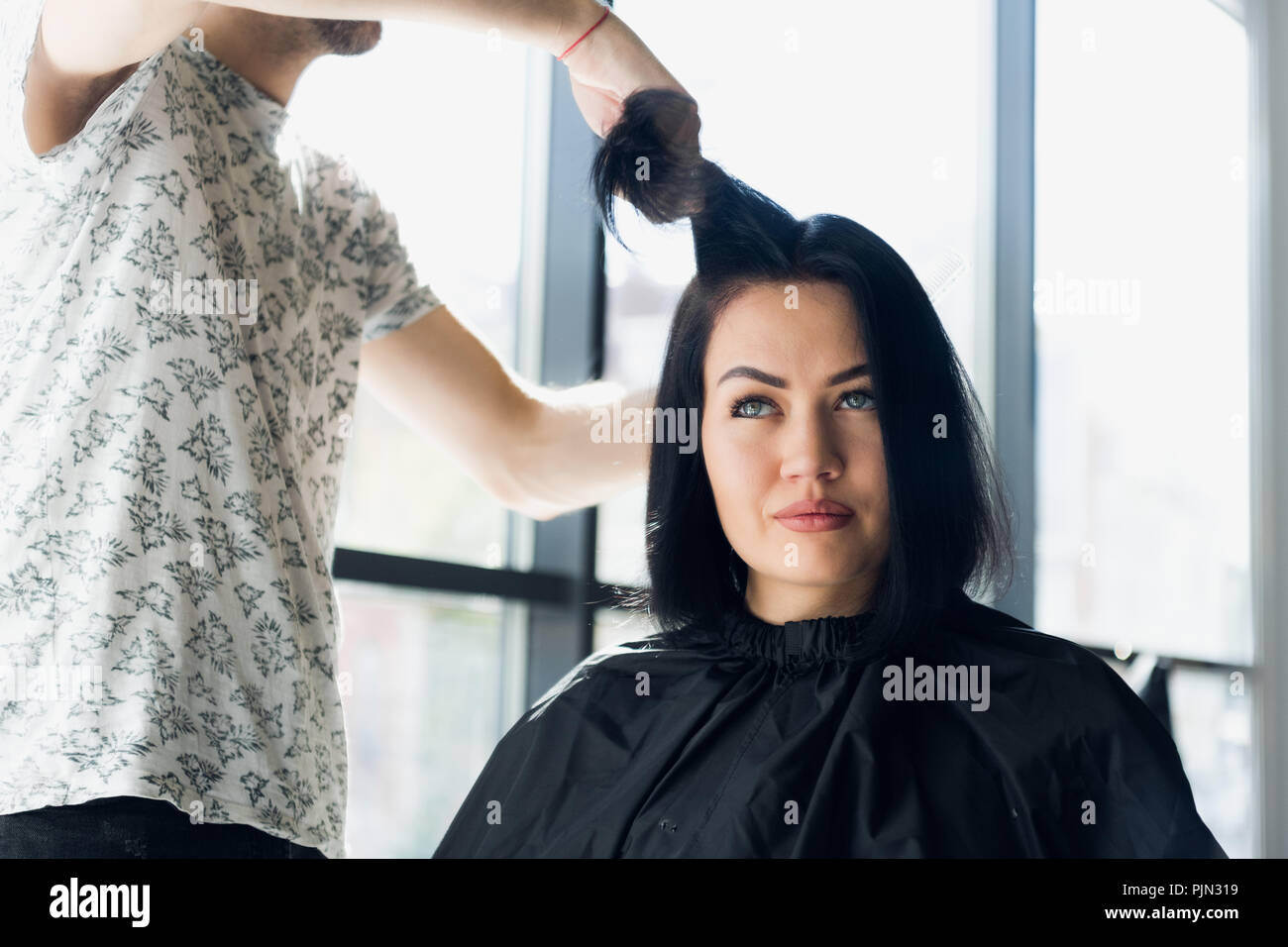 Unrecognizable hairdresser creating hairstyle for beautiful brunette woman - Stock Image